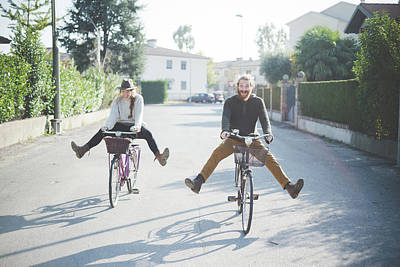 Young Couple Cycling With Legs Out Art Print by Eugenio Marongiu