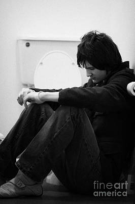 Young Dark Haired Teenage Man Sitting On The Floor Of The Bathroom With Back Against The Wall In The Art Print by Joe Fox