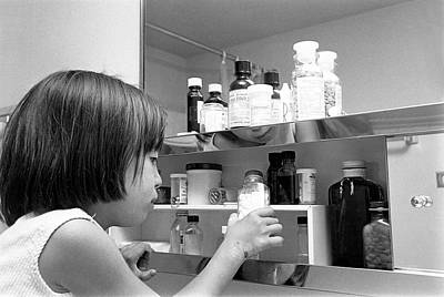 Healthcare And Medicine Photograph - Young Girl In Medicine Cabinet by Underwood Archives