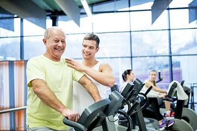 Self-confidence Wall Art - Photograph - Young Man Assisting Senior Man In Gym by Science Photo Library