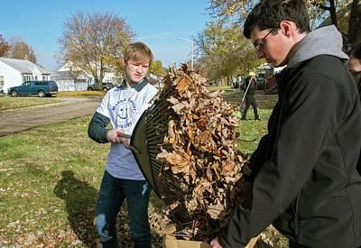 Young Volunteers Raking Leaves Art Print by Jim West