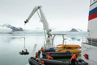 Inflatable Boats Photograph - Zodiaks Being Lifted Into The Water by Ashley Cooper