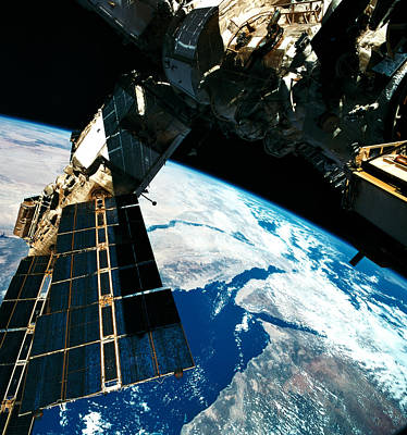 Space Exploration Photograph - A Satellite Orbiting Above The Earth by Stockbyte
