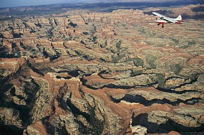 Natural Forces Photograph - A Small Aircraft Flies by Joel Sartore