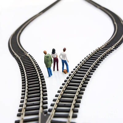 Indoor Photograph - Figurines Between Two Tracks Leading Into Different Directions Symbolic Image For Making Decisions. by Bernard Jaubert