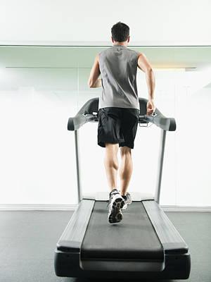 Mixed Race Man Running On Treadmill Art Print by Erik Isakson