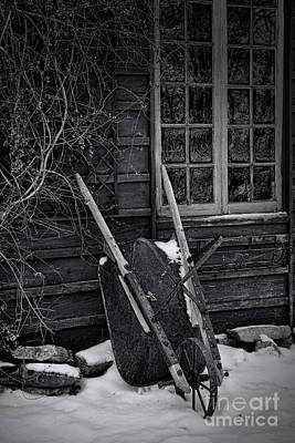 Photograph - Old Wheelbarrow Leaning Against Barn In Winter by Sandra Cunningham