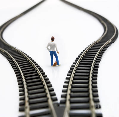 Choosing Photograph - Figurine Between Two Tracks Leading Into Different Directions Symbolic Image For Making Decisions. by Bernard Jaubert