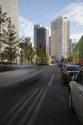 Traffic Congestion Photograph - A Car Runs Down A Street In The Central by Roberto Westbrook