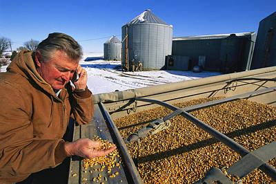 A Farmer Runs His Corn Through His Hand Print by Joel Sartore