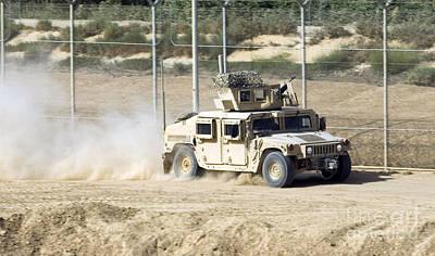 A M1114 Humvee Patrols The Perimeter Art Print by Stocktrek Images