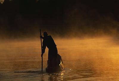 A Man Poling A Dugout Canoe Art Print by Chris Johns
