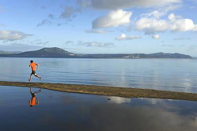 A Man Running On A Beach Is Reflected Art Print by Bill Hatcher