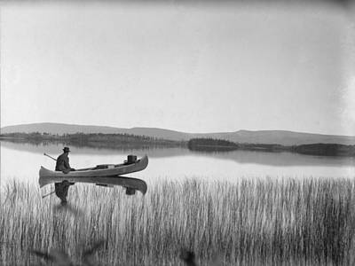 Willow Lake Photograph - A Man Sits In A Canoe On The Tranquil by George Shiras