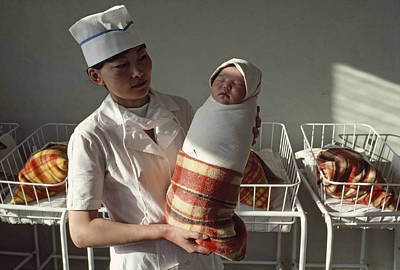 Woman And Baby Photograph - A Nurse Holds A Tightly Wrapped Newborn by Dean Conger