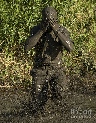 Obscured Face Photograph - A Participant Wipes Mud From His Face by Stocktrek Images