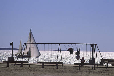 Child Swinging Photograph - A Sailboat And Kids On A Swing by Michael Melford