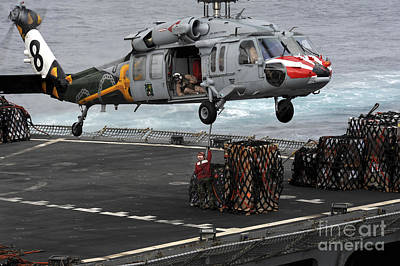 A Sailor Hooks Cargo To An Mh-60s Sea Art Print by Stocktrek Images