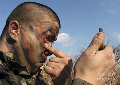 A Soldier Applying Face Paint Prior Art Print by Stocktrek Images