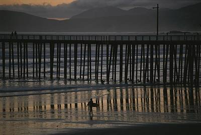 Docks Etc Photograph - A Surfer Walks Up The Beach Near A Pier by Michael S. Lewis