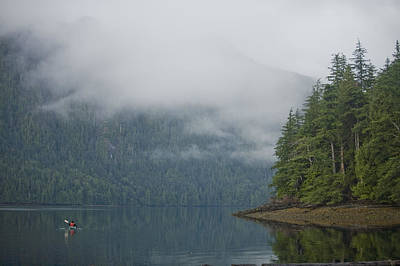 Haida Gwaii Photograph - A Woman Kayaks Along A Quiet Inlet by Taylor S. Kennedy