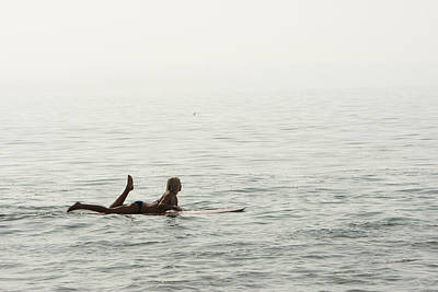 A Woman Rests On Her Surfboard Waiting Art Print by Tim Davis