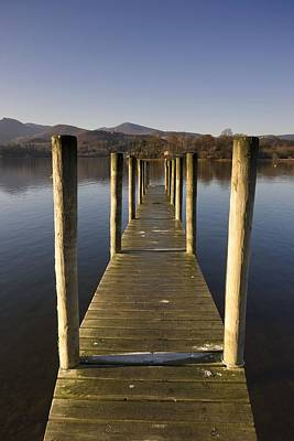 A Wooden Dock Going Into The Lake Art Print