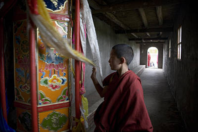 A Young Monk Spinning A Prayer Wheel Art Print by David Evans