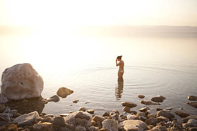 A Young Woman Wades Into The Dead Sea Art Print by Taylor S. Kennedy