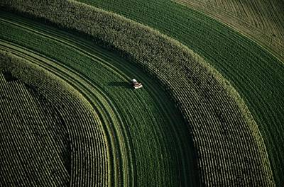 An Aerial View Of A Tractor On Curved Art Print by Paul Chesley
