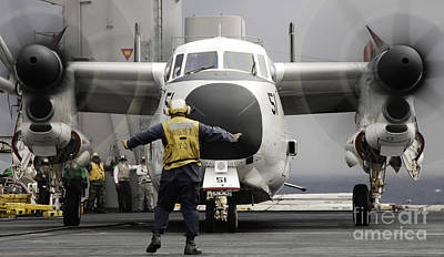 Greyhound Photograph - An Aircraft Director Guides A C-2a by Stocktrek Images