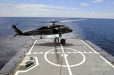 An Sh-60f Sea Hawk Helicopter Lowers Art Print by Stocktrek Images