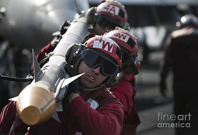 Aviation Ordnancemen Carry An Art Print by Stocktrek Images