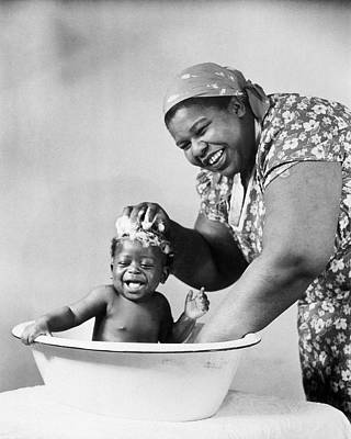 Black Woman Laughs As She Bathes Her Baby Art Print by Archive Holdings Inc.