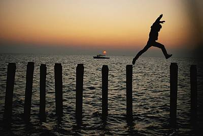 Docks Etc Photograph - Bo Hoppin Leaps Between Pilings by Robert Madden