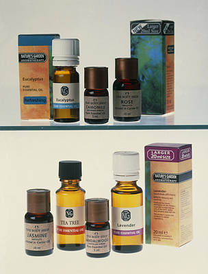 Tea Tree Photograph - Bottles Containing Aromatherapy Oils In A Cabinet by Steve Horrell