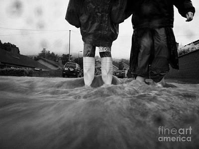 Children Walking In Heavy Rain Storm In The Street Art Print by Joe Fox