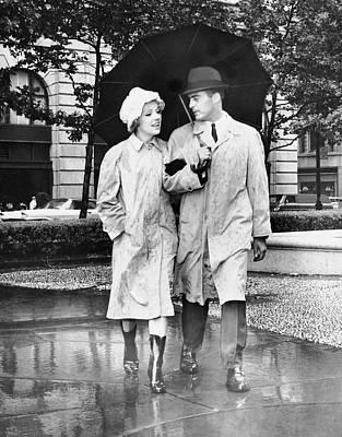 Couple W/umbrella Walking In The Rain Art Print by George Marks