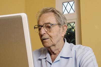 Elderly Man Using A Laptop Computer Art Print by Steve Horrell
