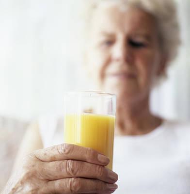 Elderly Woman Holding Glass Of Juice Art Print by Cristina Pedrazzini