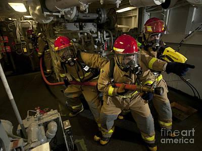 Firemen Combat A Simulated Fire Aboard Art Print by Stocktrek Images