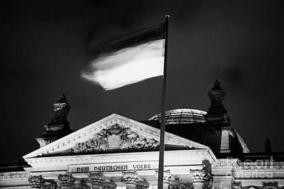 Fluttering Photograph - german flag flying fluttering on flagpole outside reichstag building Berlin Germany by Joe Fox