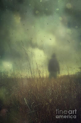 Hooded Man Walking In Field With Storm Clouds Print by Sandra Cunningham