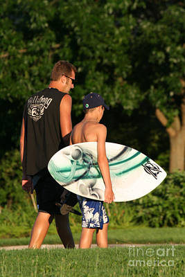 Waves Photograph - Man Walking With Teen Who Is Carrying A Skim Board by Christopher Purcell