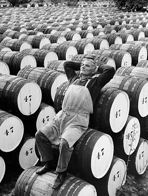 Mature Man Relaxing On Barrels (b&w) Art Print by Hulton Archive