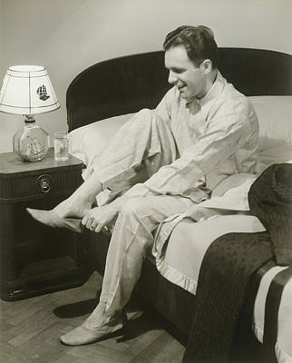 Mature Man Sitting On Bed Putting On Slippers, Smiling Art Print by George Marks