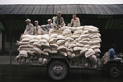 Harsh Conditions Photograph - Men Sit On Bags Of Flour by Justin Guariglia