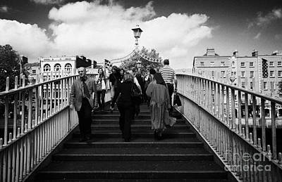 Pedestrians Crossing The Halfpenny Hapenny Bridge Over The River Liffey In The Centre Dublin Ireland Art Print by Joe Fox
