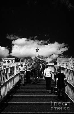 Hapenny Photograph - Pedestrians Crossing The Halfpenny Hapenny Bridge Over The River Liffey In The Centre Of Dublin City by Joe Fox