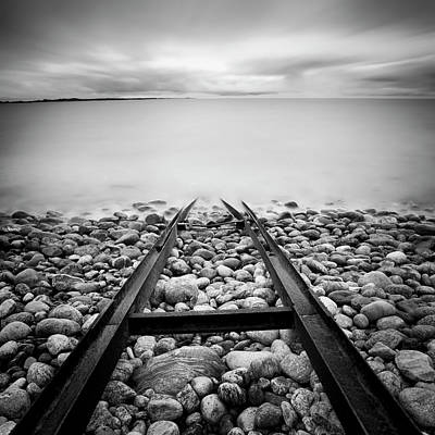 Clouds Over Sea Photograph - Railroad Tracks Into Water by Peter Levi